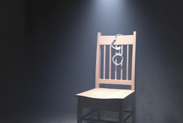 A wooden chair under a spotlight in a dark interrogation room. Very detailed high resolution 3D render.