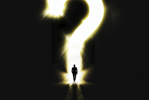 Shot of a man walking out of the darkness into a large glowing question mark